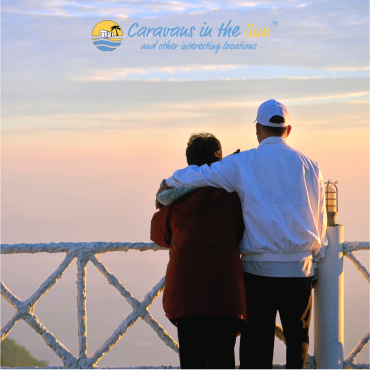 old couple hugging looking out over beach sunset
